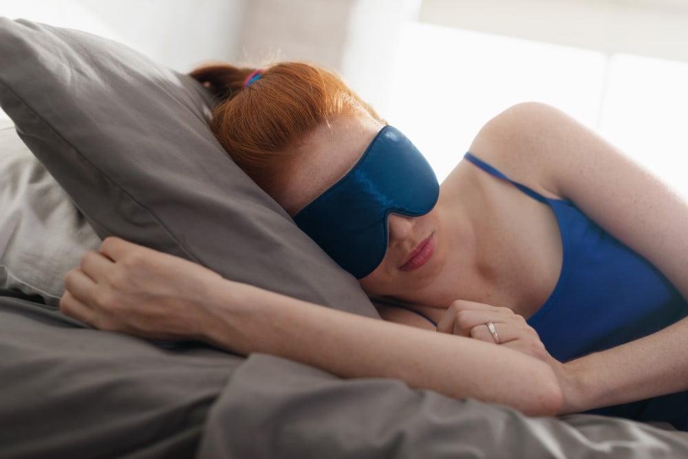 Kvinde med blå sovemaske på